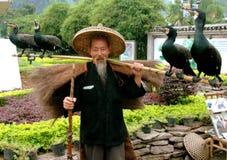 Yangshuo, Cina: Uomo con quattro uccelli di Comorrant Immagine Stock Libera da Diritti
