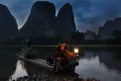 YANGSHUO - 18 DE JUNIO: Pesca china del hombre con los pájaros de los cormoranes Imagen de archivo