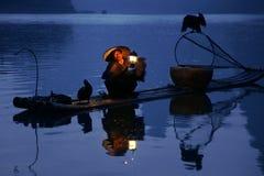 YANGSHUO - 18 DE JUNIO: Pesca china del hombre con los pájaros de los cormoranes adentro Imagen de archivo