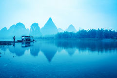 Yangshuo scenery in early morning. Photographer and raft at riverside Stock Photos