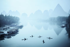 Yangshuo scenery in fog. Chinese yangshuo scenery in fog,traditional fisherman in the river Stock Photos