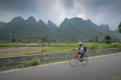 Yangshuo scenery. Local woman riding her bicycle in the country side of Yangshuo,South China Stock Photos