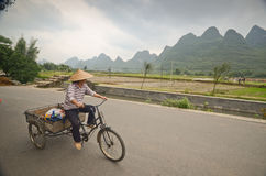 Yangshuo scenery. Local woman riding her bicycle in the country side of Yangshuo,South China Stock Image