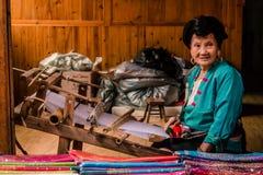 Yao Woman idosa em um tear de tecelagem fotos de stock royalty free
