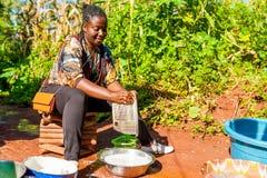 Yaounde, Cameroon - 10 august 2018: młoda zdrowa i uśmiechnięta afrykańska kobieta robi domowych obowiązek domowy domycia plenero obrazy royalty free
