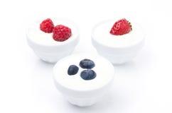Yaourt avec différentes baies fraîches dans des cuvettes sur le blanc Photos libres de droits