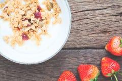 Yaourt avec la granola sur le dessus en cuvette et fraises sur en bois Image libre de droits