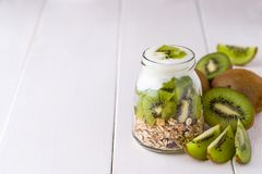 Yaourt blanc avec le muesli dans le bol en verre avec des morceaux de kiwi dessus à Photographie stock libre de droits
