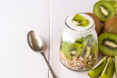 Yaourt blanc avec le muesli dans le bol en verre avec des morceaux de kiwi dessus à Image stock