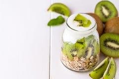 Yaourt blanc avec le muesli dans le bol en verre avec des morceaux de kiwi dessus à Photo libre de droits