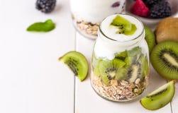 Yaourt blanc avec le muesli dans le bol en verre avec des morceaux de kiwi sur le dessus Photos stock