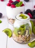 Yaourt blanc avec le muesli dans le bol en verre avec des morceaux de kiwi sur le dessus Image stock