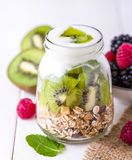 Yaourt blanc avec le muesli dans le bol en verre avec des morceaux de kiwi sur le dessus Photo stock