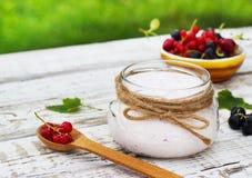 Yaourt dans un pot et une soucoupe avec des baies sur une table à l'air frais Photo libre de droits