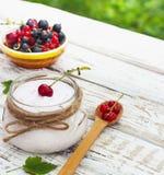 Yaourt dans un pot et une soucoupe avec des baies sur une table à l'air frais Photographie stock libre de droits