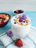 Yaourt de fromage blanc, fraise, abricot, myrtille sur un fond bleu, fleur Images libres de droits
