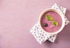 Yaourt de myrtille dans une cuvette blanche avec la feuille en bon état sur la table en bois rose Photographie stock