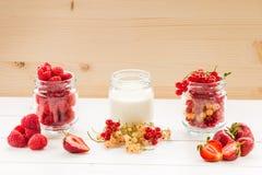 Yaourt et baie dans des pots en verre sur la table blanche au backgrou en bois Images libres de droits