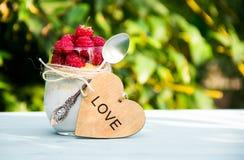 Yaourt fait maison avec des framboises Dessert de framboise de lait Coeur en bois Image stock