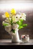 Yaourt grec avec des graines et des fruits frais de chia de noix de coco à côté des fleurs dans le vase Photographie stock libre de droits