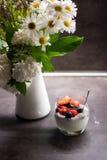 Yaourt grec avec des graines et des fruits frais de chia de noix de coco à côté des fleurs dans le vase Photographie stock
