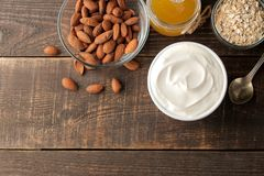 Yaourt grec dans une cuvette en céramique avec les amandes et le miel, farine d'avoine à côté d'une cuillère sur un fond en bois  image stock