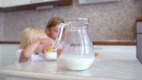 Yappy rodzina Matka stawia dalej stół dzbanek mleko w tle dwa siostry, małe dziewczynki, childs je mleko i zbiory