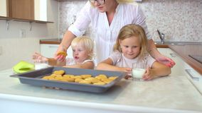 Yappy rodzina Matka stawia dalej stół szkła mleko dla dwa siostr, małe dziewczynki, childs je mleko i ciastka zbiory wideo