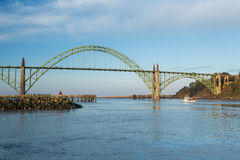 Yaquina Bay Bridge. Fishing boat leaving Newport, Oregon harbor and approaching the art deco styled Yaquina Bay Bridge on its way out to sea. US Highway 101 on Stock Images