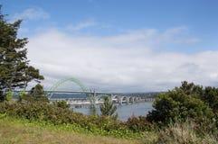 Yaquina Bay Bridge at Newport Oregon. Full span of landmark Yaquina Bay Bridge at Newport Oregon against vivid sky and framed by lush natural vegetation Royalty Free Stock Image