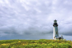 Yaquina Head Lighthouse under cloudy skies Royalty Free Stock Images