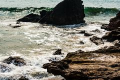 Yarada beach with indian ocean waves crashing onto the shore rocks and stones. Long exposure shot with silky smooth water and rock. Rocky sea shore looking stock photos