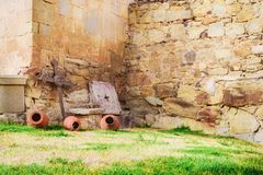 The yard of the ancient monastery with metall cross and clay pots stock image