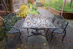 Yard in Autumn with Red Leaves , a Glass Table and Two Benches Royalty Free Stock Images
