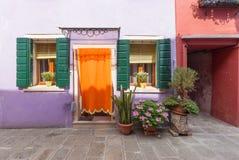Yard avec du charme et soigné plein des fleurs avec une façade colorée, des enveloppes décoratives et des portes photo libre de droits
