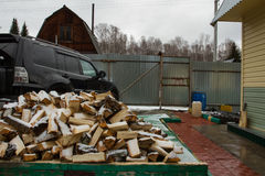 The yard of a country house. A large black SUV and a firewood over the fence. First day of winter. First snow. Firewood brought Stock Photography