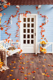 Yard of country house with tiling roof, blue wooden walls, white. Door, decorated with autumn leaves and flowers. Slipping cat on the white bench Stock Image