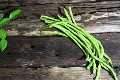 Yard long bean on wooden board background. Yard long bean on wooden board background, Dark or Classic Tone Royalty Free Stock Photos