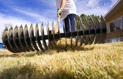 Yard maintenance. Man doing spring yard maintenance (focus on rake Royalty Free Stock Images