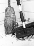 Yard Outdoor Brooms Sitting in the Corner. Monochrome oollection of yard brooms including a straw broom and bristle brooms piled in the outside corner of the Royalty Free Stock Photography