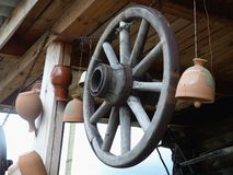 Obsolete old wheel of the horse cart. Hanging under the roof of a rural hut. Retro. Closeup. Ural, Russia.   Royalty Free Stock Image