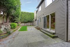 Yard privé d'une maison grise avec l'herbe verte photographie stock libre de droits