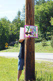 YARD SALE. A man nails a yard sale sign to a wooden post Royalty Free Stock Photo