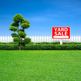 Yard sale sign. And white fence on green grass Stock Images