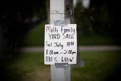 Yard sale sign. Sign of yard sale is duct taped to light post with green grass and side walk in background Royalty Free Stock Photo
