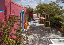 The yard of a small rose house. With tables, armchair and stairway Royalty Free Stock Image