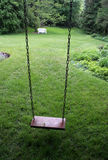 Yard Swing. An old wooden swing sitting in a lush backyard Royalty Free Stock Image