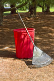 Yard Tools. Red trash can and rake sitting in preparation of yard work Stock Photos