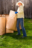 Yard work. Beautiful woman moving heavy bags of compost material in the back yard royalty free stock photo