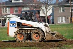 Yard work. A bulldozer digging up dirt Royalty Free Stock Photography
